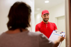Deliveryman with clipboard at customer home Royalty Free Stock Photo