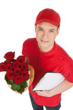 Deliveryman with flowers. Top view of deliveryman holding a bunch of roses and clipboard while standing isolated on white royalty free stock photos