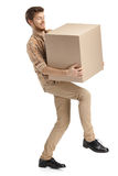 Deliveryman hardly carries the box Stock Image