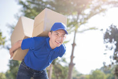 Deliveryman hold heavy box. And smile, asian Stock Photos
