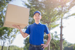 Deliveryman hold heavy box. And smile, asian Royalty Free Stock Photos