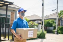 Free Deliveryman Holding Boxes. Online Shopping And Free Home Delivery. Social Distancing Stock Photo - 190217010