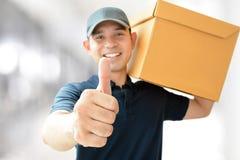Deliveryman niesie pudełko, daje aprobatom zdjęcie royalty free