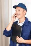 Deliveryman opowiada na telefonie komórkowym Fotografia Stock