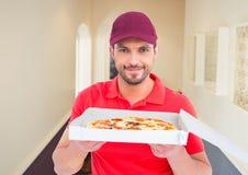 Deliveryman pokazuje pizzę w korytarzu dom fotografia stock