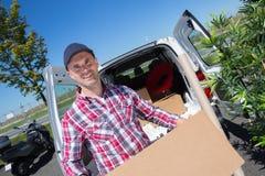 Deliveryman przewożenia pakuneczka kartonowy pudełko w frontowej dostawie obraz royalty free