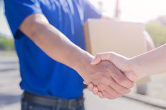 Deliveryman stand and shake hand Royalty Free Stock Image