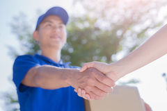 Deliveryman stand and shake hand Stock Images