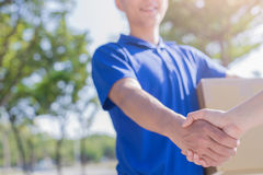 Deliveryman stand and shake hand Stock Photo