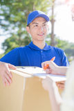 Deliveryman stand and smile Stock Images