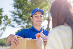 Deliveryman stand and smile. To customer, asian Stock Image