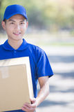 Deliveryman stand and smile Royalty Free Stock Image