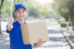 Deliveryman stand and thumb up Royalty Free Stock Photo