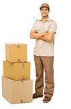 Deliveryman Standing By Stacked Cardboard Boxes Royalty Free Stock Images