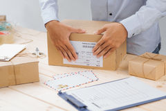 Deliveryman taping and packing cardboard box for delivery Stock Photos