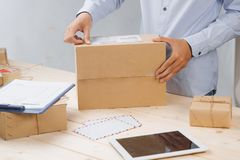 Deliveryman taping and packing cardboard box for delivery Stock Photo