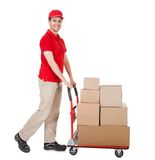 Deliveryman with a trolley of boxes. Cheerful young deliveryman in a red uniform holding trolley loaded with cardboard boxes isolated on white Royalty Free Stock Images