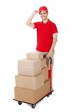 Deliveryman with a trolley of boxes. Cheerful young deliveryman in a red uniform holding trolley loaded with cardboard boxes isolated on white Royalty Free Stock Photos