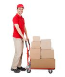 Deliveryman with a trolley of boxes. Cheerful young deliveryman in a red uniform holding trolley loaded with cardboard boxes isolated on white Stock Photography