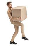 Deliveryman z trudem niesie pudełko obraz stock