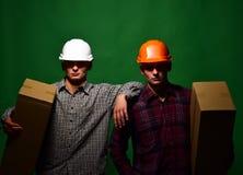 Deliverymen με τα σοβαρά κουτιά από χαρτόνι λαβής προσώπων εύκολα Στοκ Εικόνα