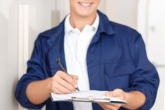 Deliverymen signing paper. Doing my job. Pleasant professional deliveryman holding folder and pen while signing paper after delivering parcel stock image