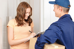 Deliverymen standing with client. Delivery with pleasure. Pleasant contented deliveryman holding parcel and giving it to client signing the paper stock images