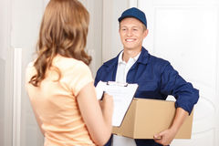 Deliverymen standing with client. Working for your comfort. Nice hilarious deliveryman holding parcel and expressing positivity while giving it to client stock photos