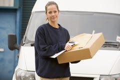 Deliveryperson die zich met bestelwagen en doos bevindt royalty-vrije stock foto