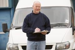 Deliveryperson die zich met bestelwagen en het schrijven bevindt Stock Afbeelding