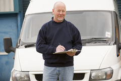 Deliveryperson restant avec le fourgon et l'inscription image stock