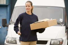 Deliveryperson standing with van with box Stock Photos