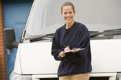 Deliveryperson standing with van writing Stock Photos