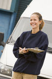 Deliveryperson standing with van writing Stock Image