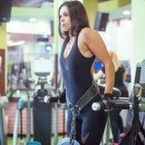 Dell'atleta della donna di allenamento le armi fuori sulle parallele simmetriche orizzontali delle immersioni esercitano il trici Immagini Stock