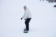 Dell'uomo di snowboard collina giù fotografia stock libera da diritti