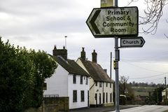 Della chiesa e della scuola primaria segnale dentro il villaggio inglese in Cambridgeshire Fotografie Stock