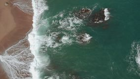 Della cima vista aerea giù delle onde di oceano che colpiscono la spiaggia sabbiosa e le rocce nel mar Mediterraneo video d archivio