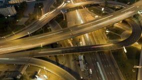Della cima vista aerea verticale giù di traffico su scambio dell'autostrada senza pedaggio alla notte archivi video
