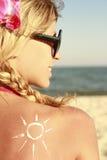 Della crema del sole sulla parte posteriore della femmina sulla spiaggia Fotografia Stock