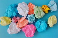 Della la carta sgualcita e sgualcita colorata multi su un fondo blu immagini stock