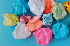 Della la carta sgualcita e sgualcita colorata multi su un fondo blu Fotografie Stock