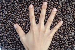Della mano i cinque chicchi del segno e di caffè del dito della mano Fotografia Stock