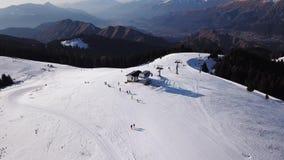 Della Presolana, Italia de Castione Opinión aérea del abejón de la gente en las cuestas del esquí y de la elevación en la estació almacen de video
