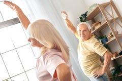 Delle coppie di esercizio sanità senior insieme a casa relativa alla ginnastica Immagini Stock