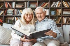 Delle coppie vista frontale senior dell'album di fotografia di concetto di pensionamento insieme a casa fotografia stock