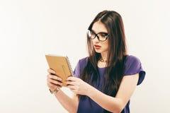 Dello studente della ragazza libro di lettura attentamente, spazio libero Ritratto della giovane donna in vetri che studing con a Immagine Stock