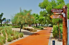 Delma Park - athletic orange elastic path. Athletic elastic path and wooden direction indicator, beautiful trees and bushes Stock Photography