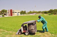 Delma Park - daily environmental cleaning. Worker in green working uniform pushing on wheel machine equipment for cleaning grass, all green around Stock Photography