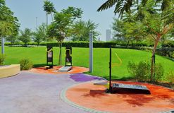 Delma Park - gym features. Gym features surrounded by Green environment of grass and trees inside orange circle Royalty Free Stock Photos